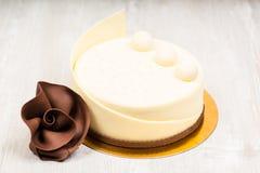 Den vita chokladkakan och steg på tabellen Royaltyfria Foton