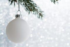 Den vita dekorativa bollen på xmas-trädet blänker på bokehbakgrund Glad julkort arkivfoton