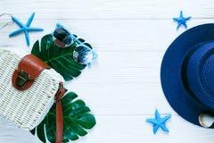 Den vita ecorottingpåsen som den tropiska djungeln gömma i handflatan monstera, lämnar sjöstjärnaskalet och en kvinnas blåa hatt  royaltyfri bild