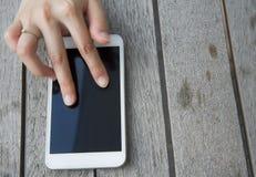 Den vita färgsmartphonen woodden på tabellen Royaltyfri Foto