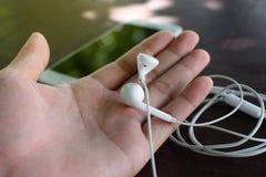 Den vita hörluren gömma i handflatan på Royaltyfria Foton