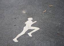 Den vita jogga manmålningen på den jogga gränden kör på ett stadigt stillar hastighet arkivbild