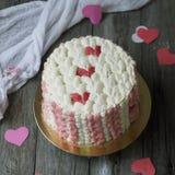 Den vita kakan med röd kräm- hjärta på träbakgrund med snör åt tyg Effekten av en stucken yttersida på kakan red steg arkivbilder