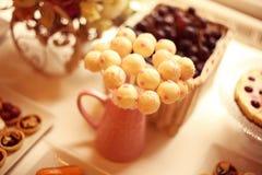 Den vita kakan poppar på tabellen Royaltyfria Foton