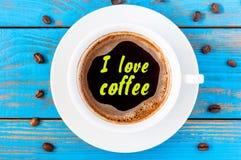 Den vita keramiska koppen med ÄLSKAR JAG KAFFEtext Stå på ett lantligt köksbord med kaffebönor Top beskådar Arkivfoton