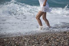 Den vita klänningen, kvinnaben som går på den tropiska stranden, semestrar Closeup av den kvinnliga unga vuxna lägre kroppen som  arkivbild