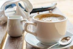Den vita koppen av läcker coffe med skum och mjölkar på stranden, når den har snorklat Royaltyfria Foton