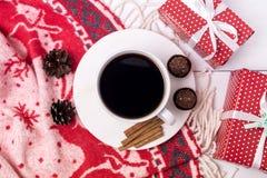 Den vita koppen av varmt kaffe på den vita bakgrundsjulen Woolen vit och röd morgon för filtkottejul frukosterar den röda gåvan royaltyfria foton