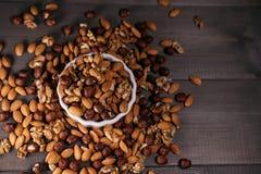 Den vita koppen fylls med muttrar Muttrar spridde omkring, hasselnötter, valnötter och mandlar ovanför sikt Fotografering för Bildbyråer