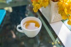 Den vita koppen häller varmt grönt te Arkivfoto