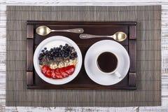Den vita koppen kaffe och sunda myslit som göras från jordgubben, blåbäret, chiafrö, havre flagar med yoghurt på ett magasin på v royaltyfri fotografi