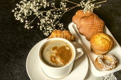 Den vita koppen med ögonblickligt kaffe och stillar blommor på svart träbräde Royaltyfri Fotografi