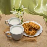 Den vita koppen med mjölkar, kakor Fotografering för Bildbyråer