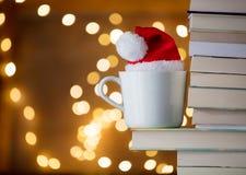 Den vita koppen och julhatten nära bokar Fotografering för Bildbyråer