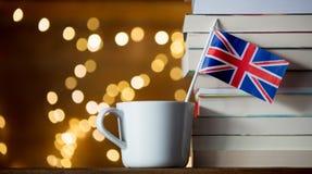 Den vita koppen och Storbritannien sjunker nära högen av böcker Royaltyfri Fotografi