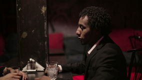 Den vita kvinnan och svarta mannen gör dialog på restaurangen Olika loppvänner stock video