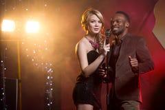 Den vita kvinnan och svarta mannen som sjunger in i en mikrofon på stången, kopplar ihop att sjunga Royaltyfri Bild
