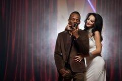 Den vita kvinnan och svarta mannen som sjunger in i en mikrofon på stången, kopplar ihop att sjunga Arkivfoton