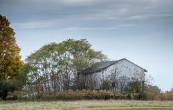 Den vita ladugården sitter mot ett färgrikt nedgånglandskap arkivfoton