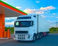 Den vita lastbilen är på bränslestationen royaltyfri foto
