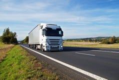 Den vita lastbilen reser på asfaltvägen i bygden, tidiga höstfärger Royaltyfri Bild