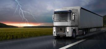 Den vita lastbilen reser på vägen i regnet royaltyfri illustrationer