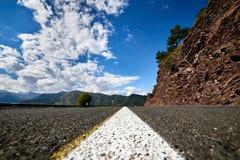 Den vita linjen på avskilja för väg vaggar och den blåa himlen royaltyfri fotografi