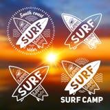 Den vita mallar för vektorkorsningen surfingbrädalogo med handen drog tecknet älskar, bor, SURFAR på den suddiga solnedgångstrand royaltyfri illustrationer