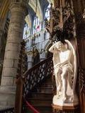 Den vita marmorstatyn snillen som är av ondo på baksidan av predikstolen i domkyrkan för St Paul ` s, Liege, Belgien arkivfoton