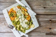 Den vita maträtten av färgad pasta fyllde med ost som överträffades med en kräm- sås Arkivbilder