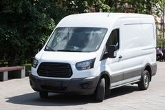 Den vita minibussen parkeras i stadsgata arkivfoton