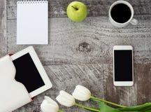 Den vita minnestavlan, telefonen, koppen kaffe, anteckningsboken, det gröna äpplet och blommor är på tabellen Arbete hemma frilan arkivbilder