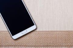 Den vita moderna smartphonen med den tomma skärmen ligger på textilen Arkivfoto
