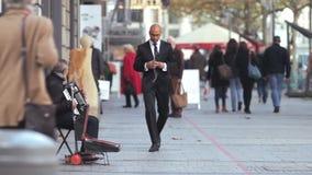Den vita musikern spelar dragspelet på gatan med svarta mannen i följe lager videofilmer