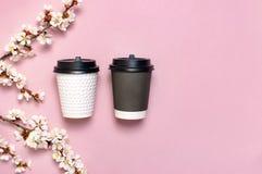 Den vita och bruna kaffe- eller tepapperskoppen p? rosa l?genhet f?r b?sta sikt f?r bakgrund l?gger Ta den bort kaffekoppen, mode arkivfoto