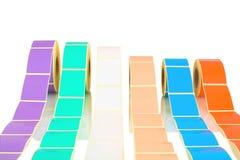 Den vita och kulöra etiketten rullar på vit bakgrund med skuggareflexion Färgrullar av etiketter för skrivare Royaltyfria Foton