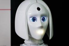 Den vita personliga roboten ser som en människa Kvinnlig framsida för härlig cyborg på bakgrunden för mörk svart arkivfoto
