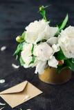 Den vita pionen blommar buketten, det tomma hälsningkortet och det pappers- kuvertet för hantverk på stenbakgrund för mörk svart  arkivbilder