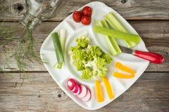 Den vita plattan fyllde med blandade grönsaker på lantlig wood bakgrund Arkivbilder