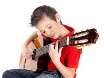 Den vita pojken spelar på den akustiska gitarren Arkivbild