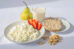 Den vita porslinplattan med ost och mogna jordgubbar, kasjuer och den genomskinliga glass koppen med mjölkar gröna päron och smäl Royaltyfri Foto