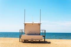 Den vita räddningsaktionen förlägga i barack på en sandig strand, kassaskåp kopplar av vid havet, en vara Royaltyfri Foto