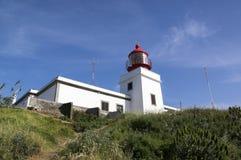 Den vita romantiska fyren på klippan, den västra madeiraön, byn Ponta gör Pargo, Portugal, Atlantic Ocean arkivbilder