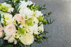 Den vita rosa färgen för bröllopbukettrosor blommar och Ruscussidor med Robbons på Gray Asphalt Background bröllop för band för i arkivbilder