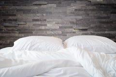 Den vita sängkläderark och kudden på den naturliga stenväggen hyr rum backg arkivbild
