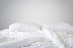 Den vita sängkläderark och kudden på den naturliga stenväggen hyr rum backg royaltyfri foto