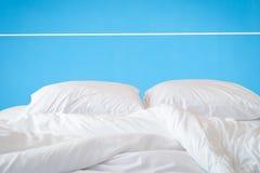 Den vita sängkläderark och kudden på den naturliga stenväggen hyr rum backg royaltyfria foton