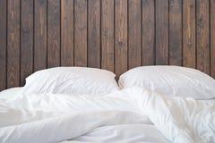 Den vita sängkläderark och kudden på träväggen hyr rum bakgrund, royaltyfri fotografi