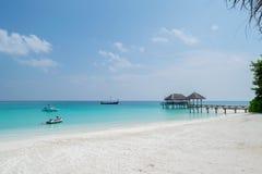 Den vita sandstranden, träbryggan, stråle skidar, motorbåten och segelbåten fotografering för bildbyråer