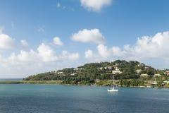 Den vita segelbåten förtöjde av kust av den tropiska ön Royaltyfri Fotografi
